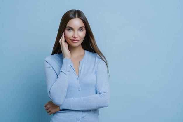 Porträt der schönen jungen frau berührt gesicht sanft, trägt blauen pullover, hat ein ansprechendes aussehen