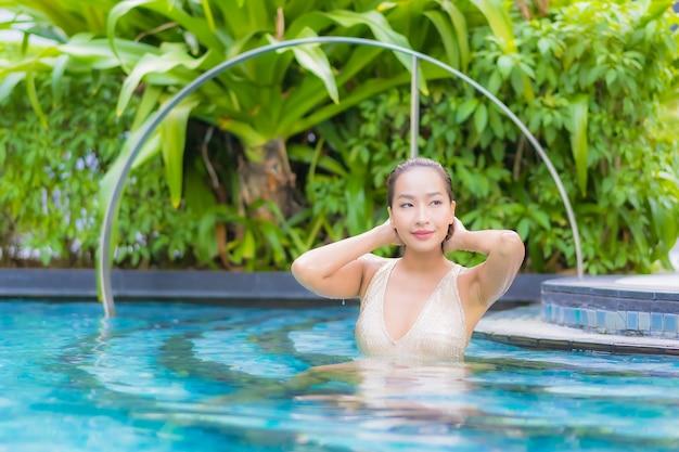 Porträt der schönen jungen frau, die am schwimmbad entspannt
