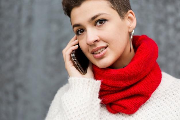 Porträt der schönen jungen frau, die am telefon spricht
