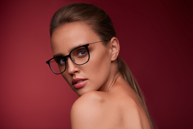 Porträt der schönen jungen frau, die brillen trägt. sinnliches model