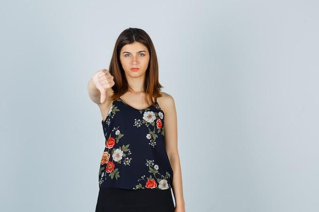 Porträt der schönen jungen frau, die daumen unten in bluse zeigt
