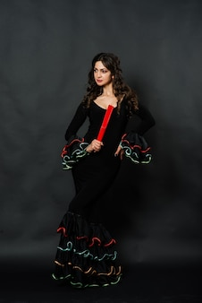 Porträt der schönen jungen frau, die flamenco mit fan im studio tanzt