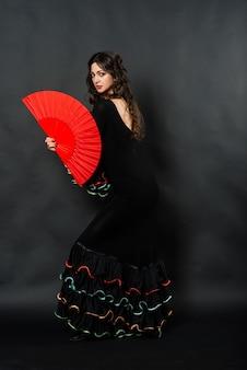 Porträt der schönen jungen frau, die flamenco mit ventilator in tanzt
