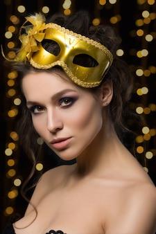 Porträt der schönen jungen frau, die goldene parteimaske mit goldenen lichtern trägt