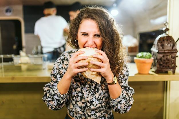 Porträt der schönen jungen frau, die hamburger im imbisswagen isst.