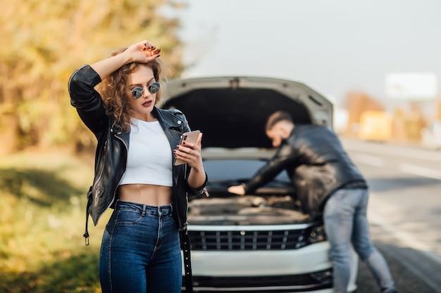 Porträt der schönen jungen frau, die ihr handy benutzt, ruft um hilfe für das auto an.