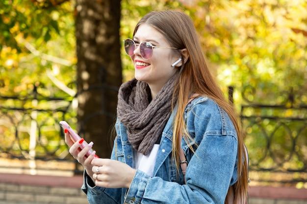 Porträt der schönen jungen frau, die ihren handy im park verwendet
