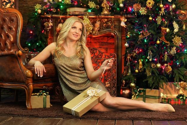 Porträt der schönen jungen frau, die im raum aufwirft, der zum weihnachtsfeiertag verziert wird