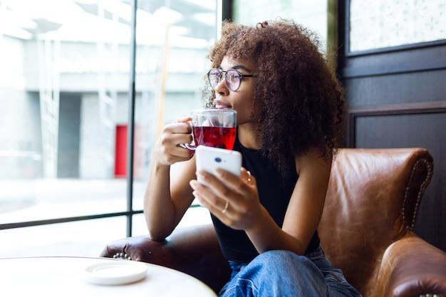 Porträt der schönen jungen frau, die kaffee im café trinkt.