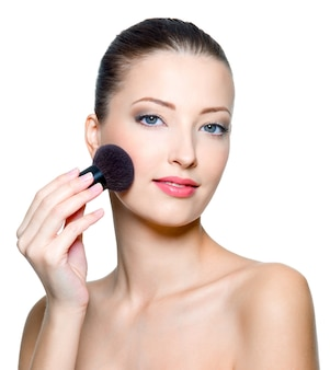 Porträt der schönen jungen frau, die make-up macht - isoliert