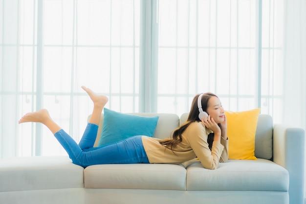 Porträt der schönen jungen frau, die musik auf sofa im wohnzimmer hört
