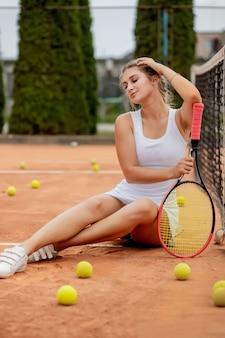 Porträt der schönen jungen frau, die nahe netz im tennisplatz mit ball im freien sitzt. selbstbewusste sportlerin, die auf tennisplatz ruht.