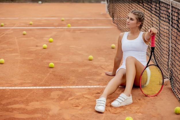Porträt der schönen jungen frau, die nahe netz im tennisplatz mit ball im freien sitzt