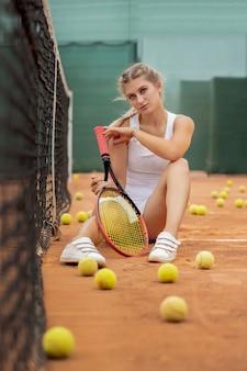 Porträt der schönen jungen frau, die nahe netz im tennisplatz mit ball im freien sitzt.