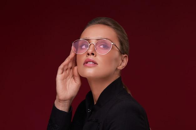 Porträt der schönen jungen frau, die rote sonnenbrille trägt. sinnliches model