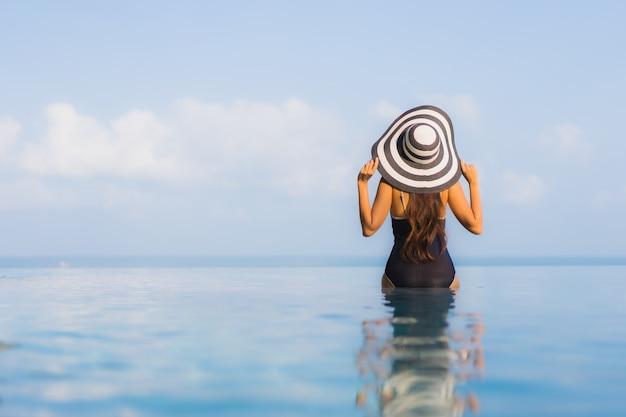Porträt der schönen jungen frau, die sich um schwimmbad im hotelresort entspannt