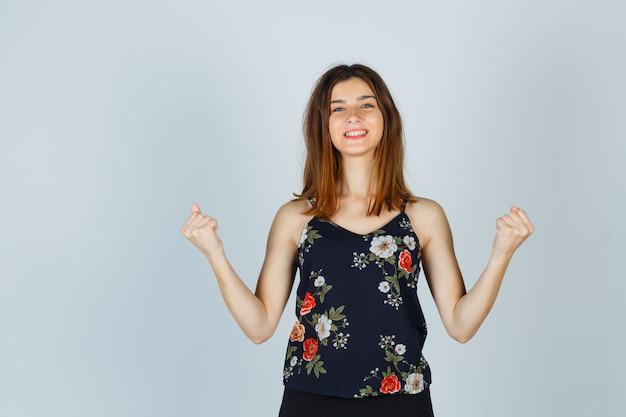 Porträt der schönen jungen frau, die siegergeste in bluse zeigt