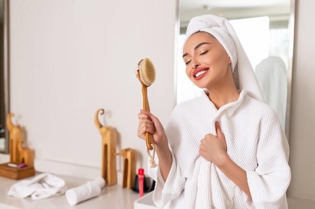 Porträt der schönen jungen frau, die süß mit den großen lippen lächelt, die massagepinsel halten