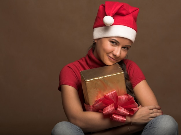 Porträt der schönen jungen frau, die weihnachtsmann-hut mit geschenk trägt