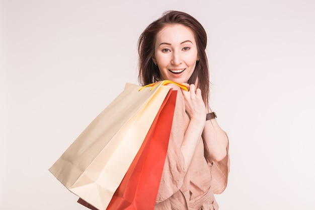 Porträt der schönen jungen frau im studio mit bunten einkaufstaschen.