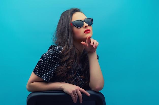 Porträt der schönen jungen frau in den gläsern auf dem schwarzen vintagen tupfenkleid an der blauen wand. junges weibliches modell.