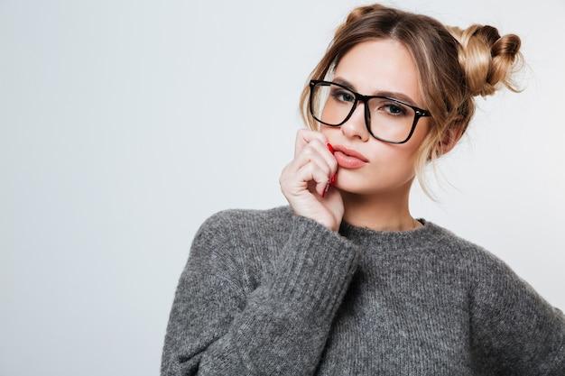 Porträt der schönen jungen frau in der brille und im grauen pullover