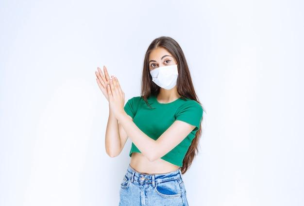 Porträt der schönen jungen frau in der medizinischen maske, die zur kamera aufwirft.