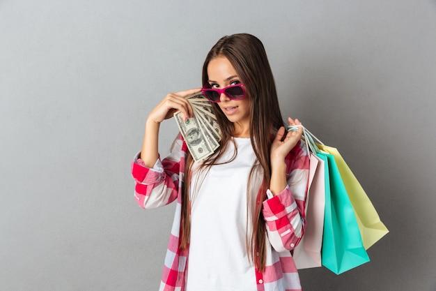 Porträt der schönen jungen frau in der rosa brille, die einkaufstaschen und dollarbanknoten hält
