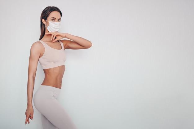 Porträt der schönen jungen frau in der sportkleidung, die schutzmaske trägt