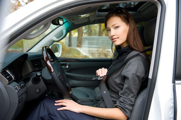 Porträt der schönen jungen frau legt einen sicherheitsgurt im auto an