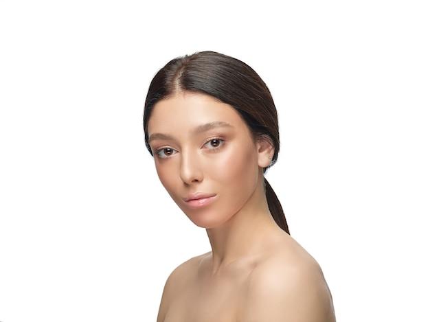 Porträt der schönen jungen frau lokalisiert auf weißer wand. kaukasisches gesundes weibliches modell und aufstellung. konzept der gesundheit und schönheit von frauen, selbstpflege, körper- und hautpflege.