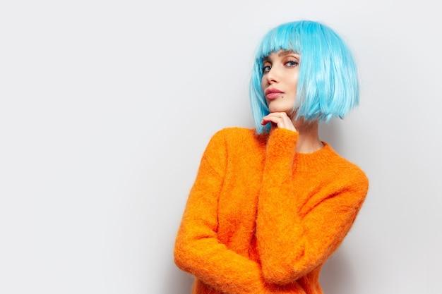 Porträt der schönen jungen frau mit blauer bob-frisur, die orangefarbenen pullover trägt