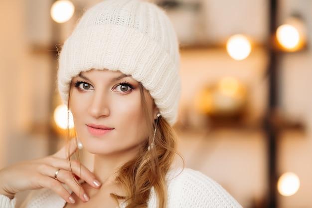 Porträt der schönen jungen frau mit blondem haar, das winterweißen wollhut und ohrringe trägt, die vorne mit gepflegter hand betrachten