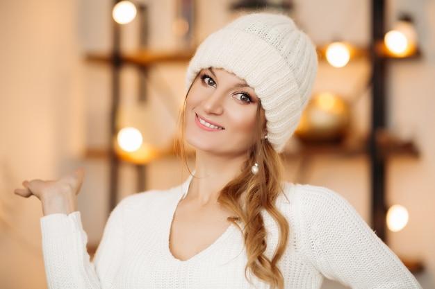 Porträt der schönen jungen frau mit blondem haar, das winterweißen wollhut und ohrringe trägt, die vorne schauen