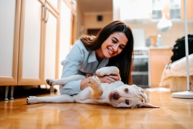 Porträt der schönen jungen frau mit dem hund, der zu hause spielt.