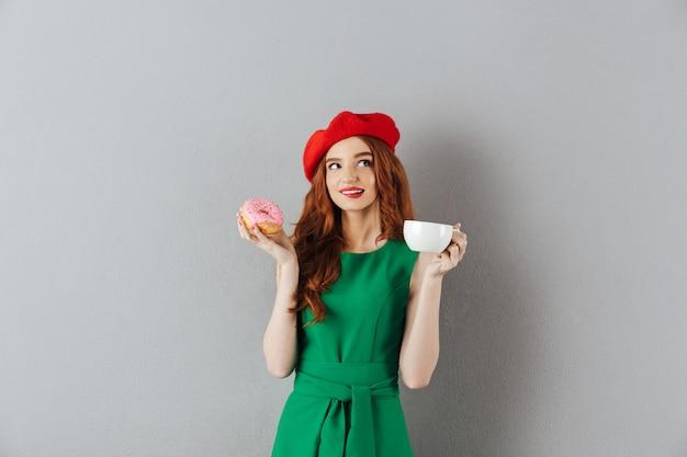 Porträt der schönen jungen frau mit dem ingwerhaar, das rote baskenmütze hält, die tasse kaffee und leckeren donut in den händen hält, lokalisiert über graue wand