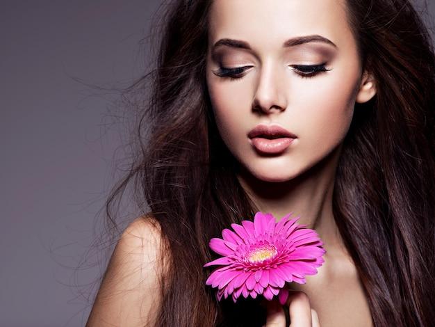 Porträt der schönen jungen frau mit dem langen braunen haar mit der rosa blume, die über dunkler wand aufwirft