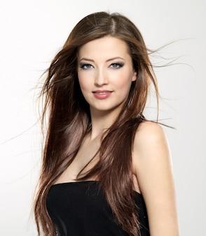 Porträt der schönen jungen frau mit dem langen geraden haar, das auf wind weht