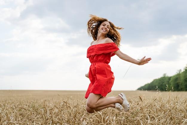 Porträt der schönen jungen frau mit dem lockigen haar in einem roten kleid in einem weizenfeld