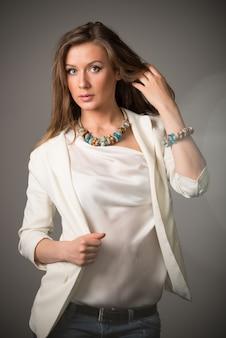 Porträt der schönen jungen frau mit den grünen augen im weißen oberteil und im massiven strickzubehör