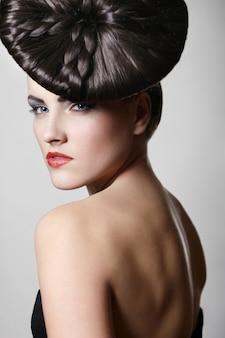 Porträt der schönen jungen frau mit den roten lippen und ungewöhnlicher frisur auf grau