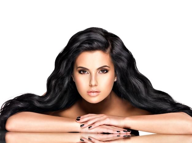 Porträt der schönen jungen frau mit den schwarzen haaren - posierend