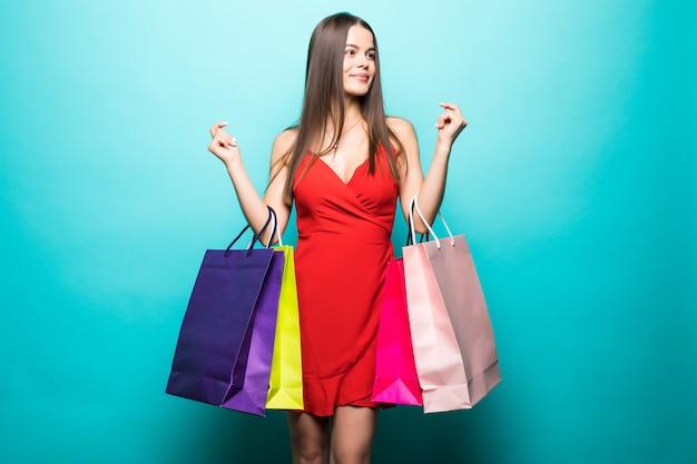 Porträt der schönen jungen frau mit einkaufstüten an der blauen wand