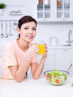 Porträt der schönen jungen frau mit frischem orangensaft und gesundem essen