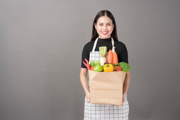 Porträt der schönen jungen frau mit gemüse in der einkaufstüte im grauen hintergrund des studios