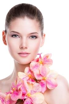 Porträt der schönen jungen frau mit gesunder haut und rosa blumen auf körper - lokalisiert auf weiß