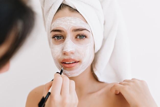 Porträt der schönen jungen frau mit handtüchern nach dem bad machen kosmetische maske auf ihrem gesicht.