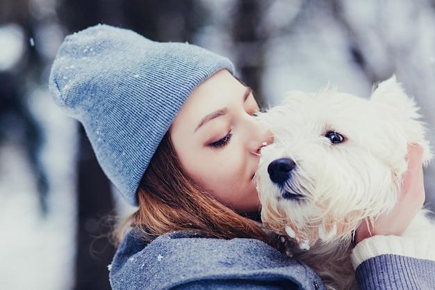 Porträt der schönen jungen frau mit hund im winter