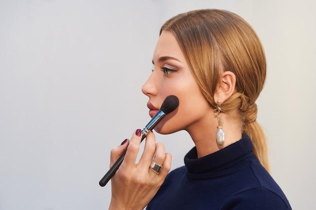 Porträt der schönen jungen frau mit langen blonden haaren und hellem make-up