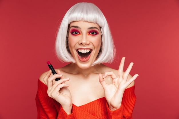 Porträt der schönen jungen frau mit leuchtend rotem make-up lokalisiert auf der roten wand, die lippenstift hält.